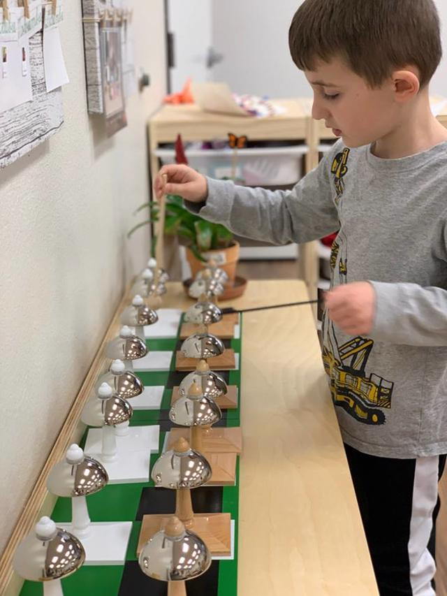 Best Private Montessori School Frisco, TX Student works on fine arts bells from Middle C to High C
