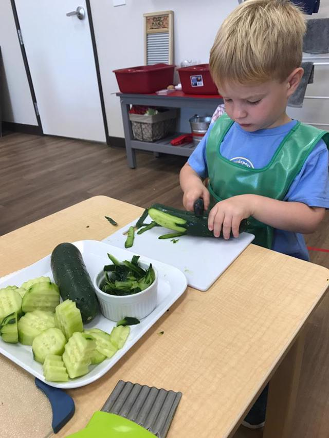 Best Private Montessori School Frisco, TX Student works independently cutting vegetables at Guidepost Montessori at Stonebriar