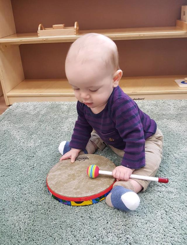 Nido student playing drum builds gross motor skills at Guidepost Montessori in Frisco, TX | Private School