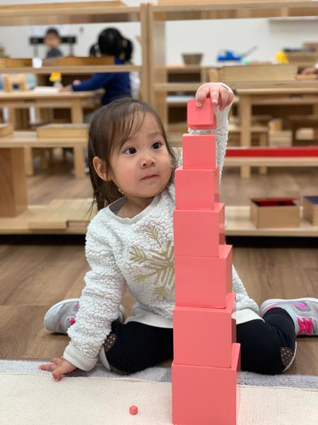 Student works on pink tower traditional montessori Frisco, TX Guidepost at Stonebriar