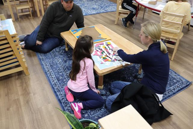 Elementary student shows her parents the United States puzzle map with the names of the states. As she continues on this geography lesson, she will identify the state capitals at Guidepost Montessori in Frisco, TX | Best private school
